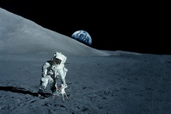 Astronaut is walking on the moon. With land on the horizon. Elements of this image were furnished by NASA. High quality photo