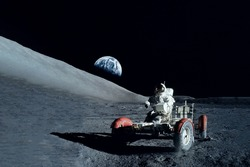 Astronaut near the moon rover on the moon. With land on the horizon. Elements of this image were furnished by NASA. High quality photo