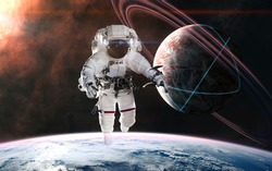 Astronaut on background of planets in deep space. Glowing structures on surface of planet with rings. Science fiction. Elements of this image furnished by NASA