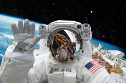 Astronaut on space mission with earth on the background. Elements of this image furnished by NASA.