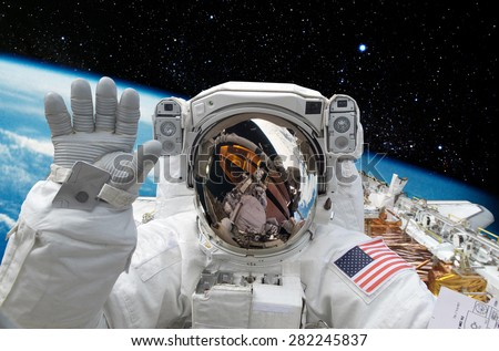 Astronaut on space mission with earth on the background. Elements of this image furnished by NASA. Imagine de stoc ©