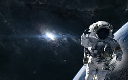 Astronaut on the background of a bright star in the center of the galaxy. Deep space planet. Science fiction. Elements of this image furnished by NASA