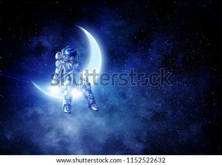 Astronaut sit on crescent moon. Mixed media