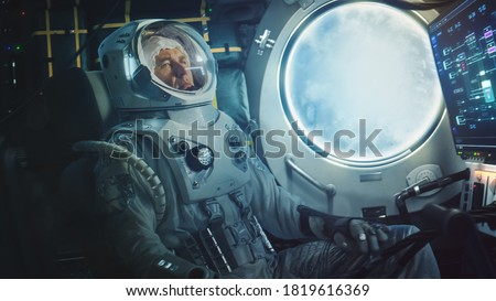 Astronaut Sitting Inside a Space Rocket During Take Off. Successful Rocket Launch Sending Space Ship into Space. Cosmonaut Experiencing G-Force and Vibrations Inside Capsule. Clouds in Porthole. Сток-фото ©
