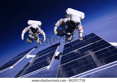 Astronauts in space around the solar panels