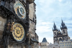 Astronomical clock of in Old Town of Prague with Tyn church at the background