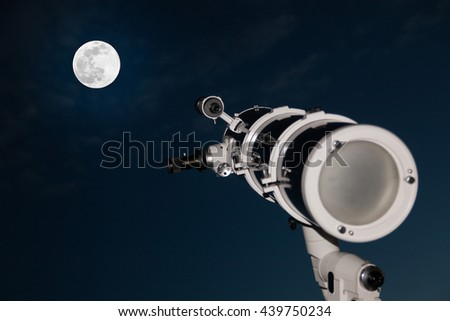 Astronomical telescope over dark sky with the moon in the night