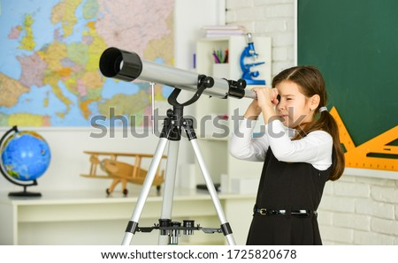 Photo of  Astronomy and Astrophysics. Stars and galaxies. Study telescope. School astronomy lesson. School girl looking through telescope. Telescope tripod in classroom. School hobby club. Observation concept.
