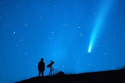 Astronomy lover with a telescope observing a comet in the blue starry sky at night. Silhouette of a person observing the immensity of the universe and the stars. Trace of a comet or a shooting star.