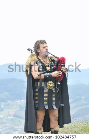 ASTURIAS, SPAIN - AUGUST 21: Celtic piper playing the bagpipes in a representation of the battle between Romans and Astures on August 21, 2011 in Asturias, Spain.