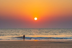 At beach, Indian woman fully indulged watching the setting Sun above the sea. Clean beach and vibrant colours giving contrast to the image. Intentional focus on Sea to display vastness of the area.