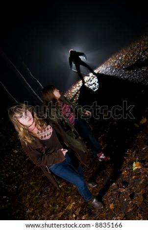 At dark night on a wood the maniac follows girls - stock photo