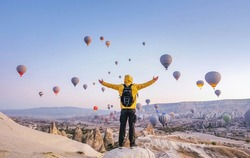 At dawn a tourist with a backpack on the background of soaring hot air balloons in Cappadocia, Turkey, concept achievement, team, leader