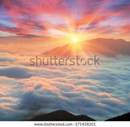 At dawn, after a warm rain ridges Chornogory haze enveloped with rays of sunshine. Sea fog in the pink light is very beautiful and fabulous, picturesque vague wave rolled on the slopes of the peaks #371428201