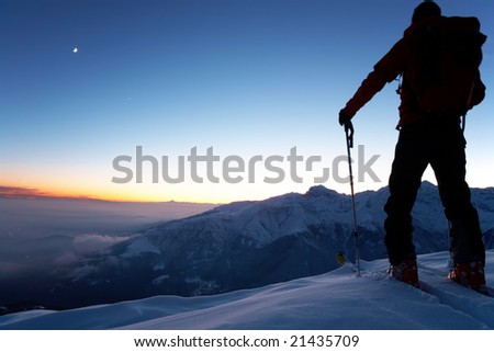 At dusk a brave backcountry skier reaching the summit of the mountain after a long day walking in the wilderness. Adventure and exploration concept.
