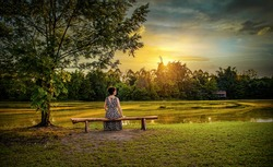 At dusk, a woman sitting on a long wooden bench by a lake was enjoying the beautiful scenery