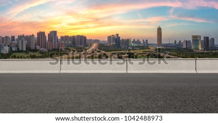 At dusk, Zhengzhou cityscape with asphalt road and city skyline in foreground #1042488973