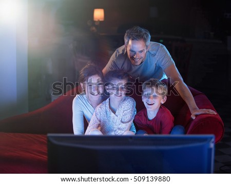 At home by night, Cheerful family sitting in a red couch and watching a funny movie on tv. They are laughing togetherness. Shot with flare