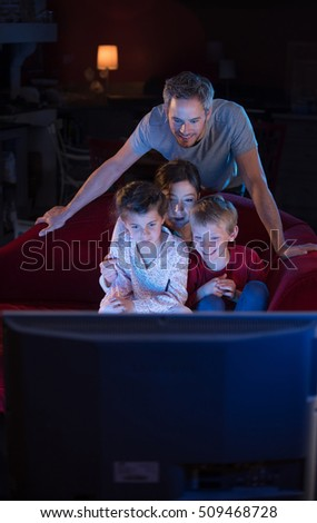 kids watching tv at night. detail · at home by night, cheerful family sitting in a red couch and watching funny kids tv night