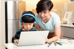 At-home learning, new normal daily routine for kids. A smart asian boy using laptop computer to study from home during Covid-19 pandemic lockdown with his mother. Online education, Homeschooling.