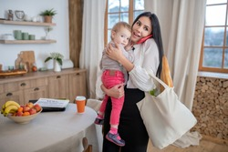At home. Mom holding daughter and shopping bag, talking on the phone, smiling