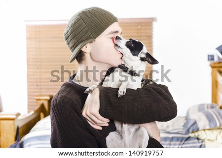 At home portrait of a small dog kissing his male owner. Pet love