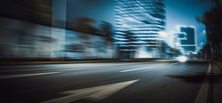 At night, wide motion blurred roads on the side of urban high-rise buildings