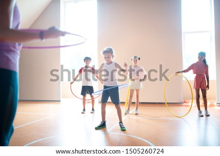 At physical training. Boys and girls wearing sport clothing rolling hula-hoops at physical training