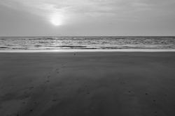 At sunset, a lone bird flies quickly over the beach with footprints but no one