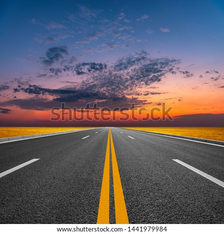 At sunset, sunlight on the grassland converges with the skyline on a tarmac road stretching to the distant mountains.