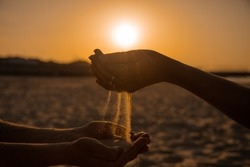 At sunset, two young people pour Golden sand from hand to hand, showing warm feelings. A symbol of eternal love and transience of life time on Earth.