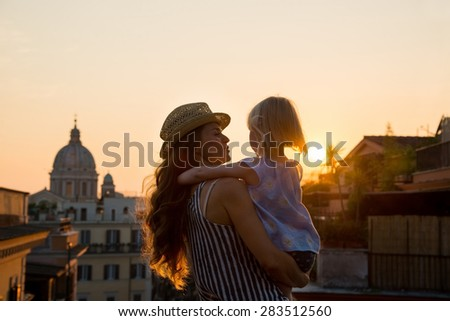 At sunset, with views over Rome, a brunette mother wearing a hat is holding her daughter - seen from behind - in her arms, and talking to her. In the distance, St. Peter\'s Basilica.