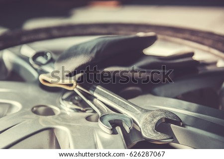 At the auto service. Auto mechanic's equipment. Tools, gloves on wheel #626287067