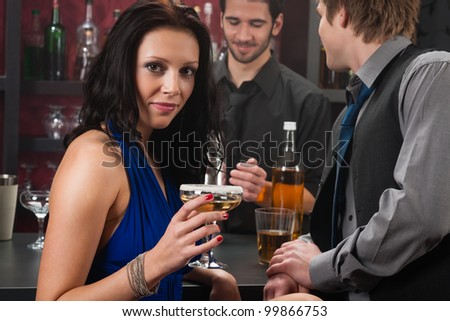 At the bar attractive young woman drink sitting with friend