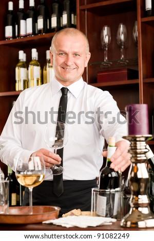 At the bar - waiter hold bottle white wine in restaurant