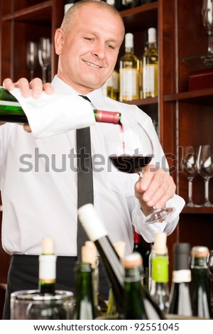 At the bar - waiter pour red wine in glass restaurant #92551045