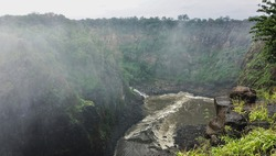 At the bottom of the Victoria Falls Gorge, the Zambezi River boils and foams. A spray fog hangs over the precipice. Lush vegetation around. In the foreground there are picturesque wet stones, grass