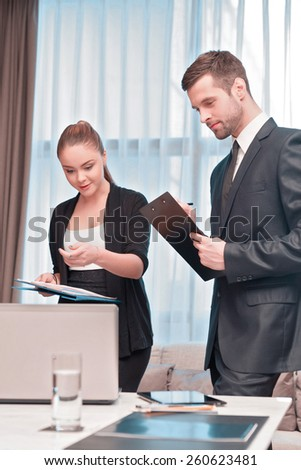 At the business meeting. Two cheerful business people in formal wear looking at the laptop together and pointing at something