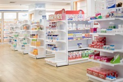 At the chemist, Medicines arranged in shelves, Pharmacy drugstore retail Interior blur abstract background with medicine healthcare product on cabinet with neon light.