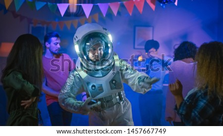 At the College House Costume Party: Fun Guy Wearing Space Suit Dances Off, Doing Robot Dance Modern Moves. With Him Beautiful Girls and Boys Dancing in Neon Lights.