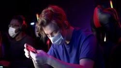 At the computer club, a cute guy in a medical mask plays a game through an app on his smartphone