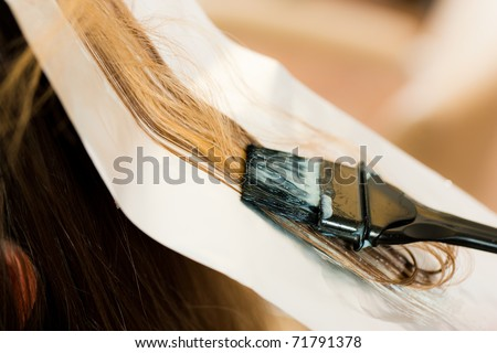 At the hairdresser � woman gets new hair colour; close-up on strand of hair