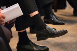 At the meeting, a man's legs crossed in black trousers. Socks in short trousers.