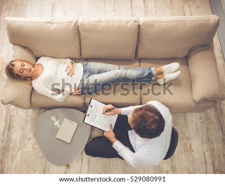 At the psychologist. Top view of beautiful young woman lying on couch while doctor is making notes
