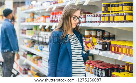 At the Supermarket: Beautiful Young Woman Browses through the Canned Goods Section of the Store. She Checks Nutritional Value of Strawberry Jam. She Has Shopping Basket Full of Healthy Food Items. #1275256087
