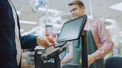 At the Supermarket: Checkout Counter Customer Pays with Smartphone for His Food Items. Big Shopping Mall with Friendly Cashier, Small Lines and Modern Wireless NFC Paying Terminal System.