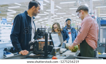 At the Supermarket: Checkout Counter Professional Cashier Scans Groceries and Food Items. Clean Modern Shopping Mall.