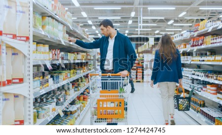 At the Supermarket: Handsome Man Browses Through Shelf with Canned Goods, Looks at Tin Can but Decided not to Buy it. He Walks with Shopping Cart Through Different Sections of the Store.