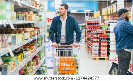 At the Supermarket: Handsome Man Browses Through Shelf with Canned Goods, Looks at Tin Can. Walking with Shopping Cart Through Different Sections of the Store.