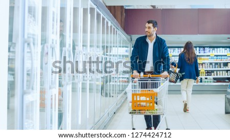 At the Supermarket: Handsome Man Pushes Shopping Card and Browses for Products in the Frozen Goods Section. Man Looks into Glass Door Fridge, Looking for Dairy Products. Other Customer in Backgrounds